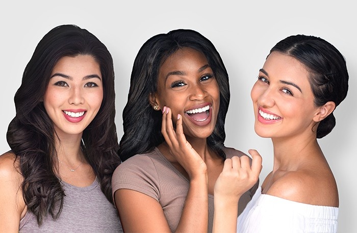 Mixed race multi-ethnic female friends laughing together perfect smile
